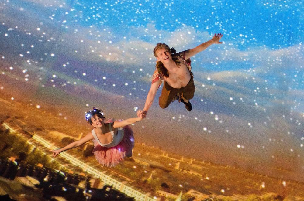 "Tinker Bell (Emily Yetter) and Peter Pan (Chuck Bradley) fly to Neverland in the threesixty° stage production of ""Peter Pan,"" performed in the theater tent on Boston's City Hall Plaza. (Andrew Brilliant/Brilliant Pictures Inc.)"