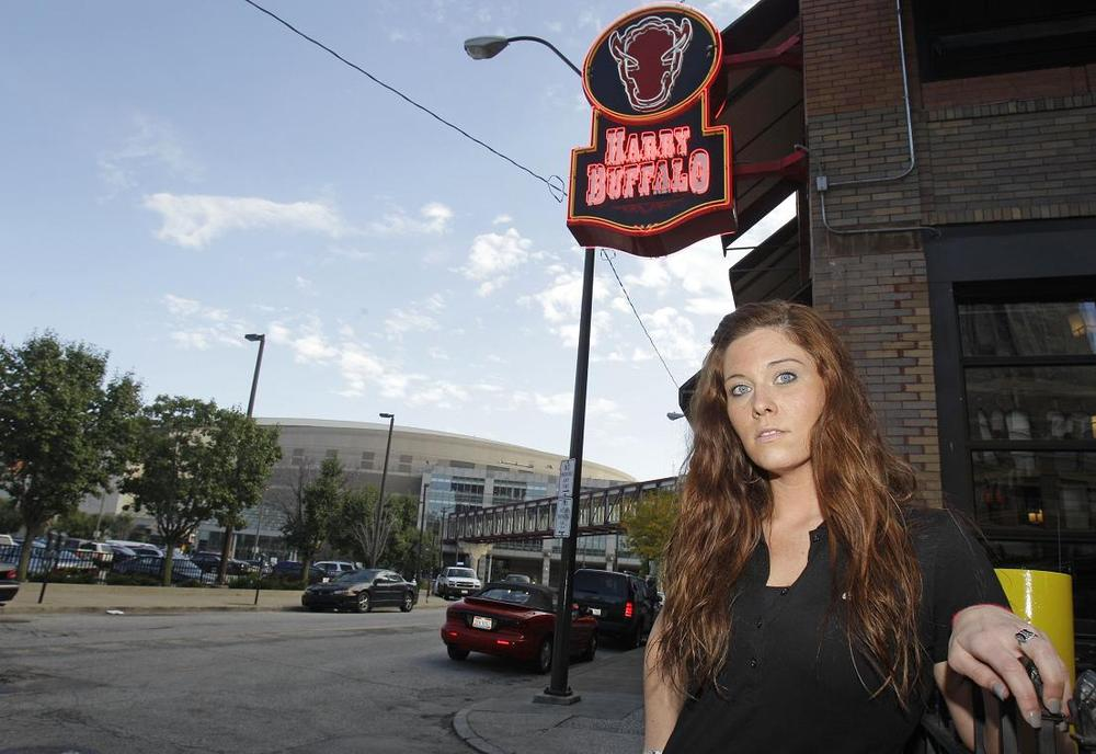 Caitlin Cassidy, a manager at the Harry Buffalo, sits at a table with the Quicken Loans Arena in the background, in Cleveland. (AP)