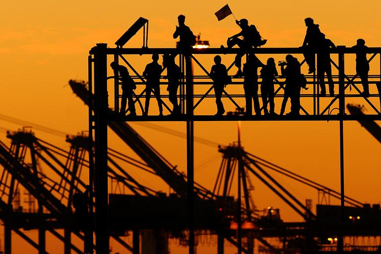 Occupy Oakland protesters stand atop a railroad scaffold at the Port of Oakland on Wednesday, Nov. 2, 2011, in Oakland, Calif. Thousands of Wall Street protesters took to Oakland's streets as part of a day-long series of events, called a citywide strike, aimed at asserting the movement's strength and shutting down commerce. (AP)
