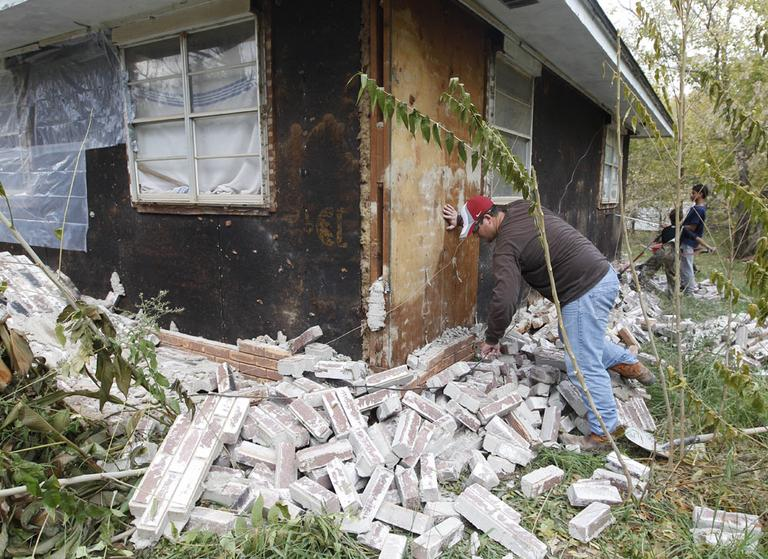 Chad Devereaux works at cleaning up the bricks that fell from three sides of his in-laws home in Sparks, Okla., Sunday, Nov. 6, after two earthquakes hit the area in less than 24 hours. (AP)