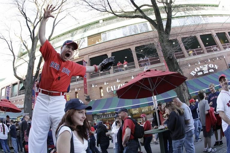 A stilt-walker performs outside Fenway Park before a Boston Red Sox game on April 4, 2010. (AP)