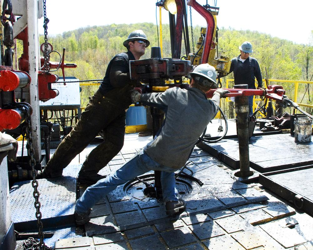 Workers move a section of well casing into place at a Chesapeake Energy natural gas well site near Burlington, Pa. (AP)