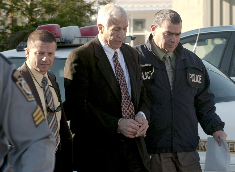 "In this photo provided by the Pennsylvania Office of Attorney General, former Penn State football defensive coordinator Gerald ""Jerry"" Sandusky, center, is escorted in handcuffs to a waiting police car in Bellefonte, Pa. to be taken to the office of a Centre County Magisterial District judge on Saturday, Nov. 5, 2011. Sandusky is charged with sexually abusing eight young men. (AP/Pennsylvania Office of Attorney General, Commonwealth Media Services)"