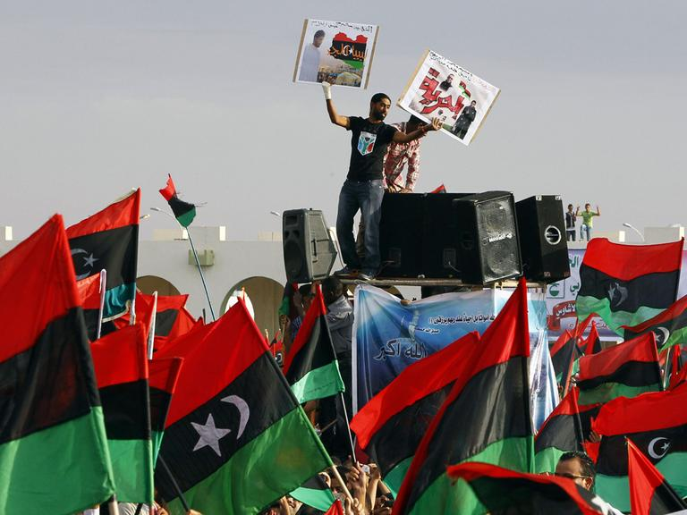 A Libyan wounded youth holds up portraits of martyrs during the celebration at Saha Kish Square in Benghazi, Libya, Sunday Oct. 23, 2011 as Libya's transitional government declare liberation of Libya after months of bloodshed that culminated in the death of longtime leader Moammar Gadhafi. (AP)