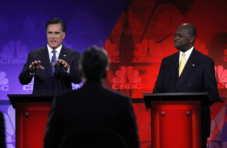 Republican presidential candidate and former Massachusetts Gov. Mitt Romney, left, speaks as Herman Cain listens during a Republican presidential debate at Oakland University in Auburn Hills, Mich., Wednesday.  (AP)