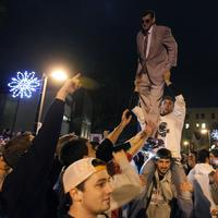 Penn State students and others gather off campus, one holding a cutout of football coach Joe Paterno, Wednesday. (AP)