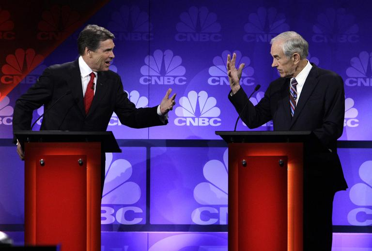 Republican presidential candidates Texas Gov. Rick Perry and Texas Rep. Ron Paul speak during a Republican presidential debate at Oakland University in Auburn Hills, Mich., Wednesday. (AP)