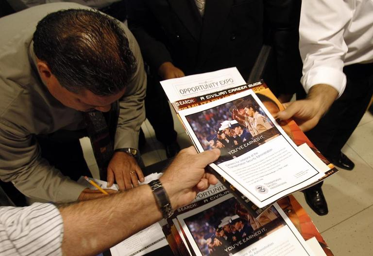 People receive information packets as they sign-in to attend the Opportunity Expo held by RecruitMilitary, Thursday, in Miami. (AP)