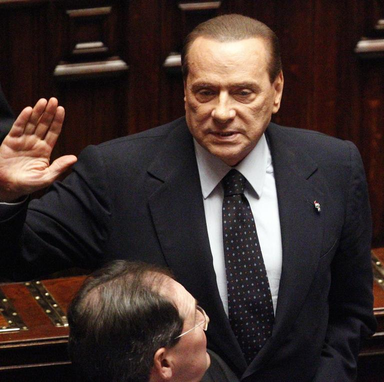 Italian Premier Silvio Berlusconi acknowledges the applause before leaving the Lower Chamber in Rome, Saturday. (AP)