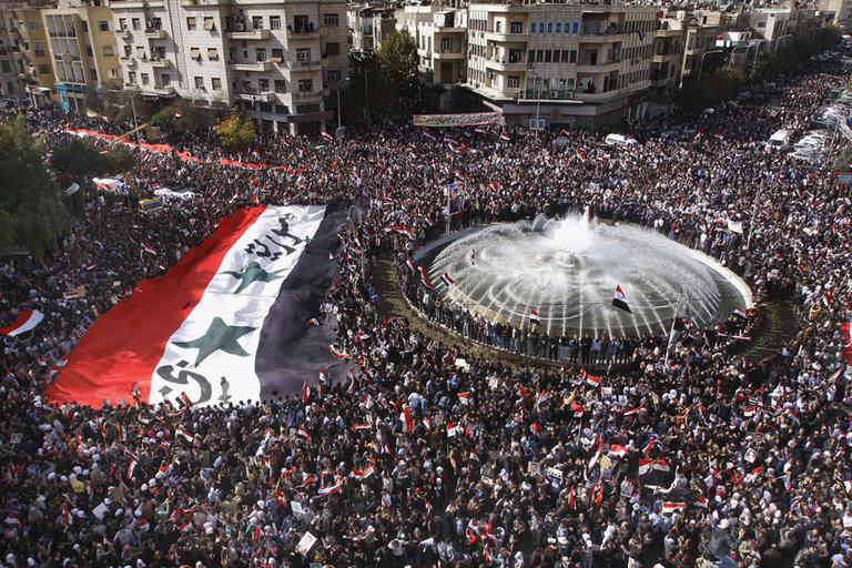 Pro-Syrian regime protesters, carry a giant Syrian flag during a demonstration against the Arab League decision to suspend Syria, in Damascus, Syria, on Sunday Nov. 13. (AP)