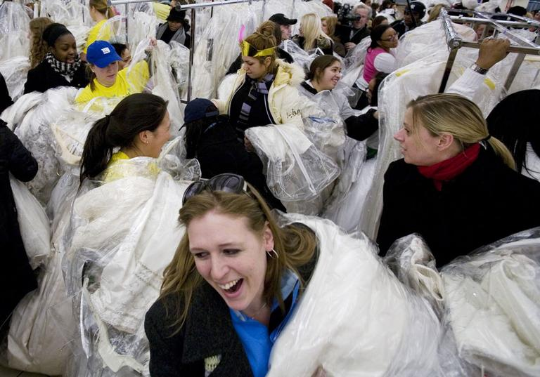 "Women grab dresses at a ""Running of the Brides"" sale at Filene's Basement in New York. (AP)"