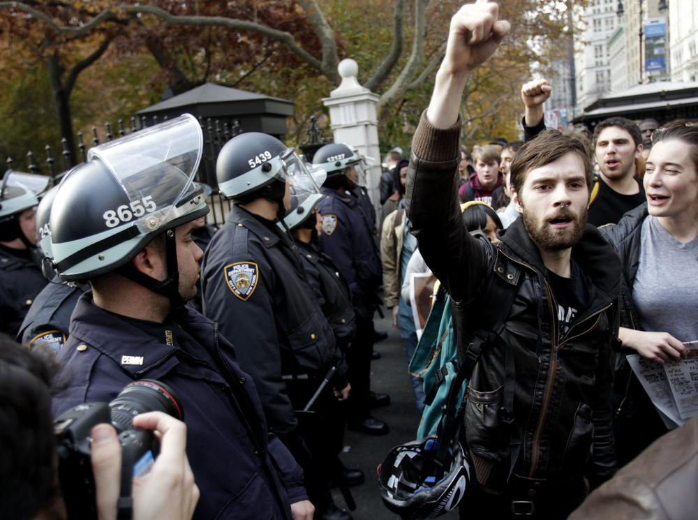 Police in riot gear watch as Occupy Wall Street protesters march past City Hall in New York, Tuesday. (AP)