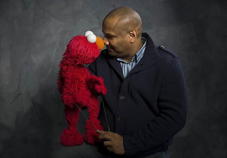 """Elmo and puppeteer Kevin Clash of the film """"Being Elmo"""" poses for a portrait in the Fender Music Lodge during the 2011 Sundance Film Festival. (AP Photo/Victoria Will)"""