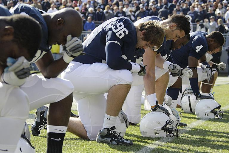 Penn State football players kneel in prayer before an NCAA college football game against Nebraska in State College, Pa. (AP Photo/Gene J. Puskar)