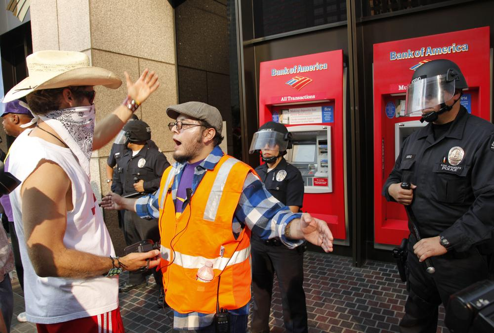 Occupy Los Angeles organizers, center, keep protesters away from confronting Los Angeles police officers guarding a Bank of America ATM in Los Angeles, Thursday. (AP)