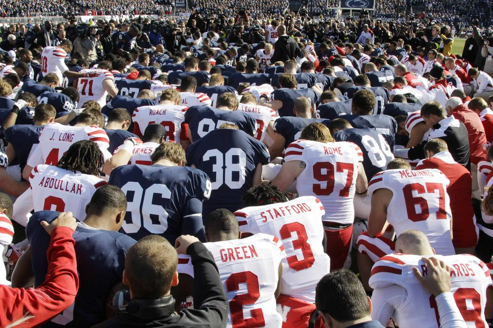 Penn State and Nebraska football players gather at midfield for a prayer before Saturday's game in State College, Pa. (AP)