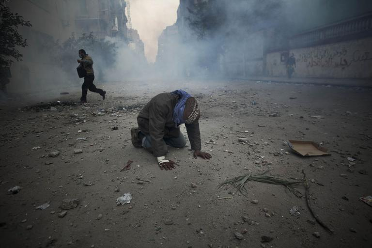 A protester overcome with tear gas inhalation kneels in the middle of the street during clashes with the Egyptian riot police, not seen, near the interior ministry in downtown Cairo, Egypt, Sunday, Nov. 20. (AP)