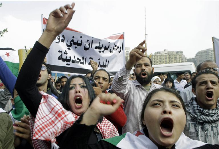 """Syrian protesters shout anti-Syrian Preident Bashar Assad slogans during a protest in front of the Arab League headquarters in Cairo, Egypt, Saturday, Nov.12, 2011 where the League emergency session on Syria is to discuss the country's failure to end bloodshed caused by government crackdowns on civil protests. Protesters called the Arab League to suspend the country's membership. Arabic read """" step out, we need to build civilian modern country"""" (AP)"""