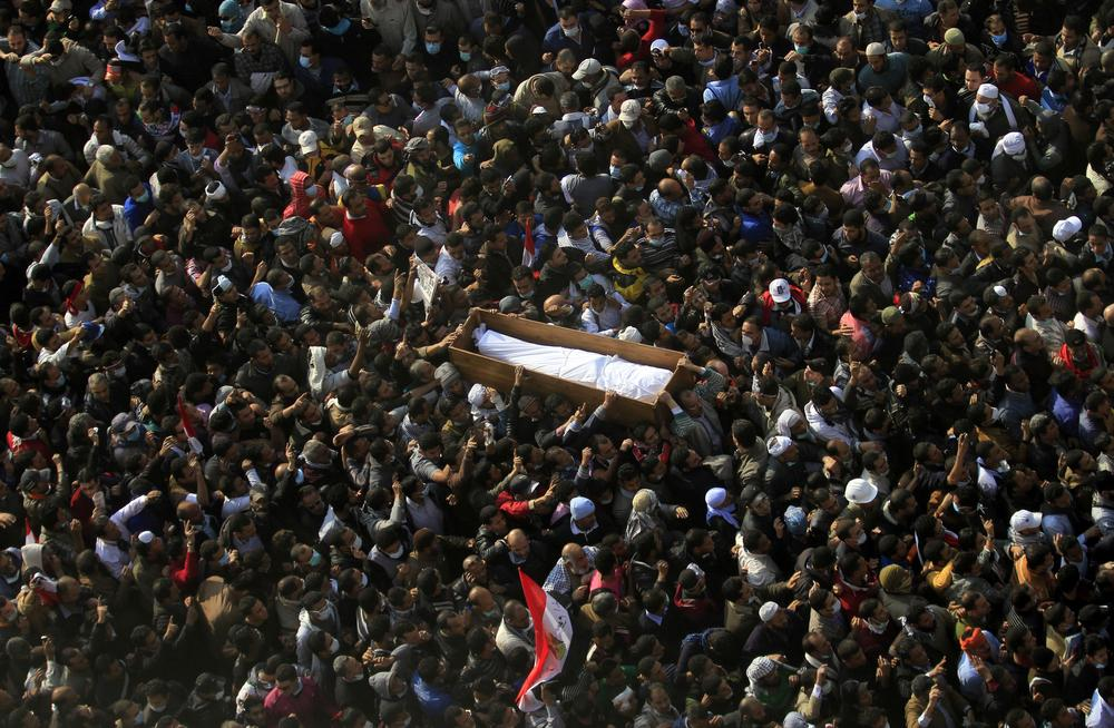 Egyptians carry a body of a protester was killed in clashes with the Egyptian riot police during his funeral at Tahrir square in Cairo, Egypt on Tuesday. (AP)