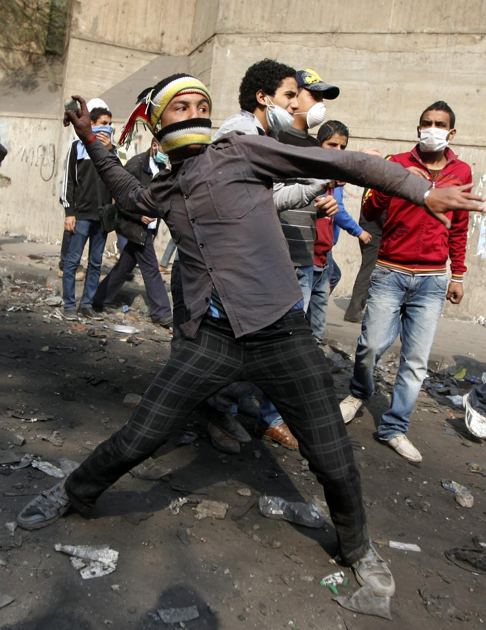 A protester throws stones during clashes with the Egyptian riot police near Tahrir square in Cairo, Egypt on Tuesday. (AP)