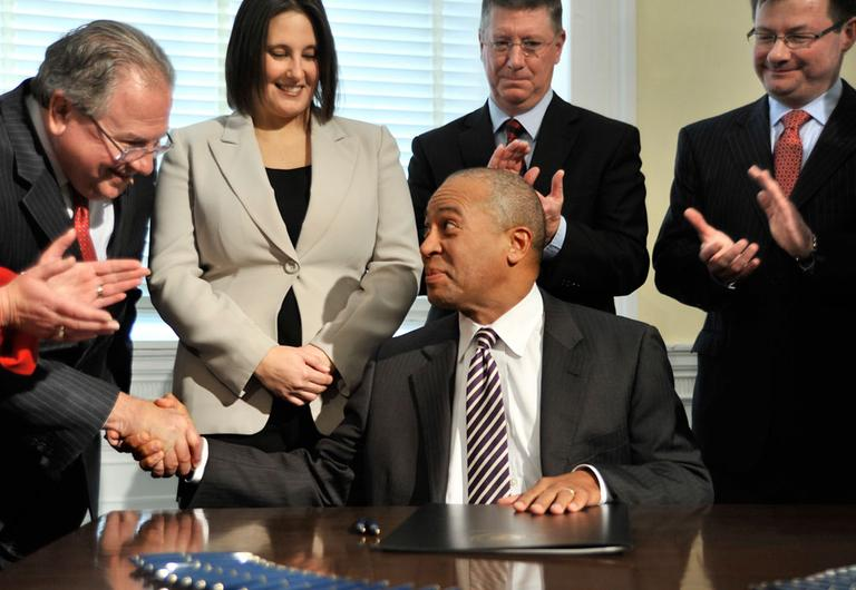 As others look on, Gov. Deval Patrick shakes hands with Speaker Robert DeLeo after signing a bill legalizing casino gambling in Massachusetts Tuesday. (AP)