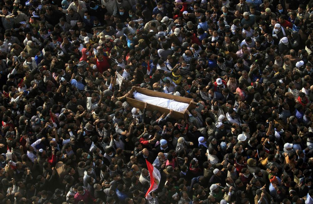 Egyptians carry a body of a protester, killed in recent clashes with the Egyptian riot police, at Tahrir square, during his funeral on Tuesday in Cairo, Egypt. (AP)