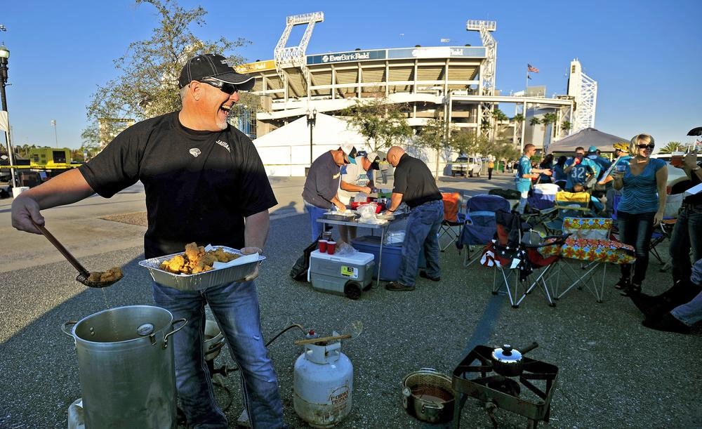 Jacksonville Jaguars fan Eric Alexander deep fries fish while tailgating before an October game. (AP)