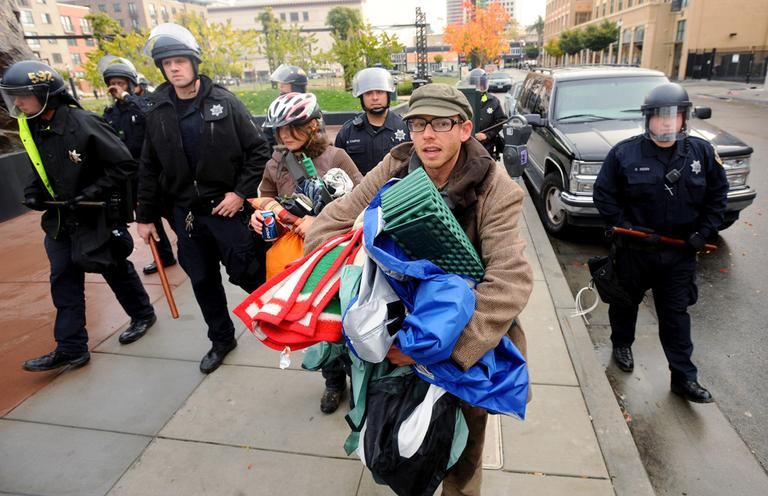 Police officers evict Occupy Oakland protesters from their camp at Telegraph Avenue and 19th Street in Oakland, Calif., on Sunday, Nov. 20, 2011. The previous night, protesters tore down a fence surrounding a vacant lot to establish the 20-tent encampment. (AP)