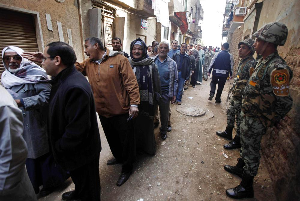 Egyptian army soldiers stand guard as voters line up outside a polling center in Assuit, south of Cairo, Egypt. (AP)