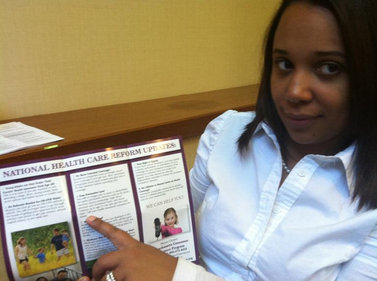 Arelis Gomes points out the free preventive care information in her Health Care for All brochure. (Martha Bebinger/WBUR)