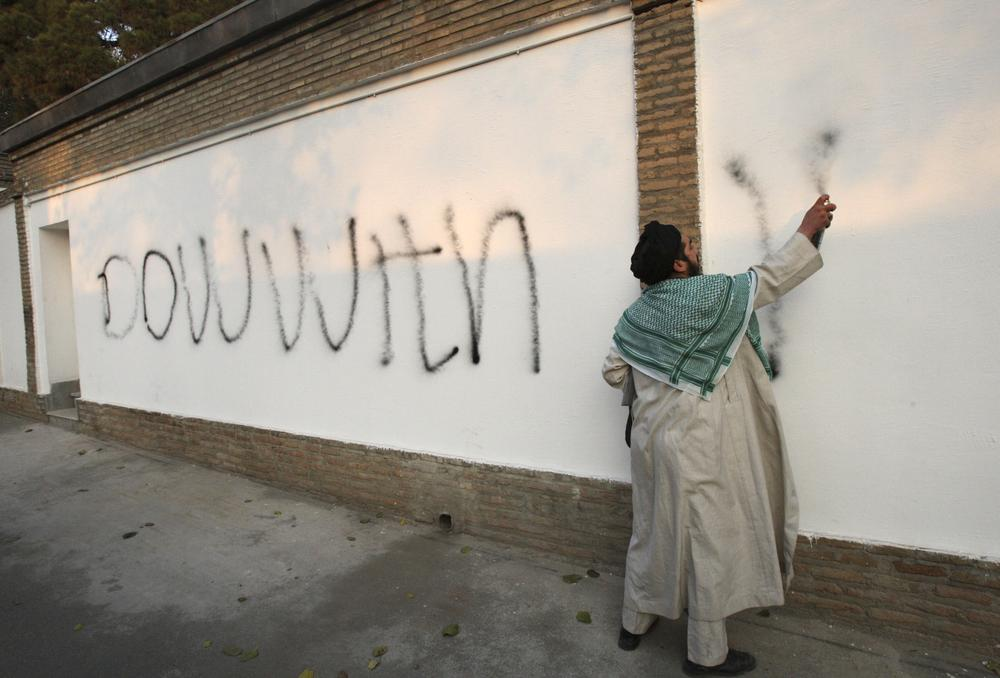 An Iranian cleric spray paints graffiti on the inside wall of the British Embassy while demonstrators stormed the embassy, in Tehran, Iran. (AP)