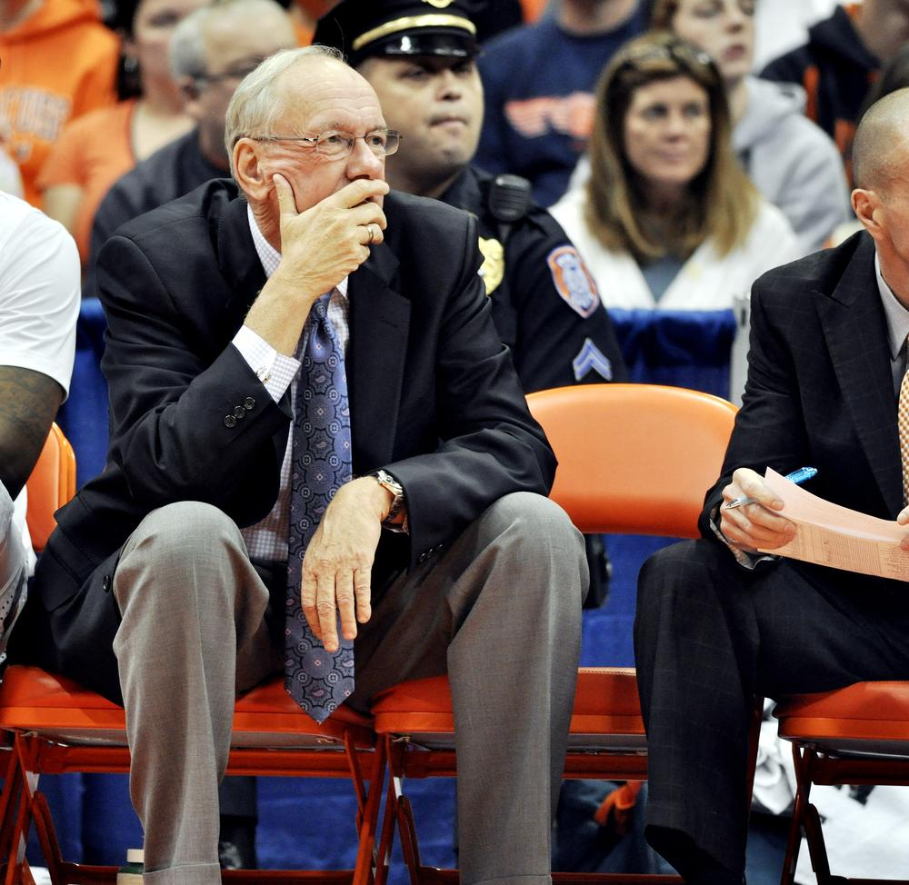 Syracuse head coach Jim Boeheim watches the game beside the empty chair of associate head coach Bernie Fine during the first half of an NCAA college basketball game against Colgate in Syracuse, N.Y., Saturday. (AP )