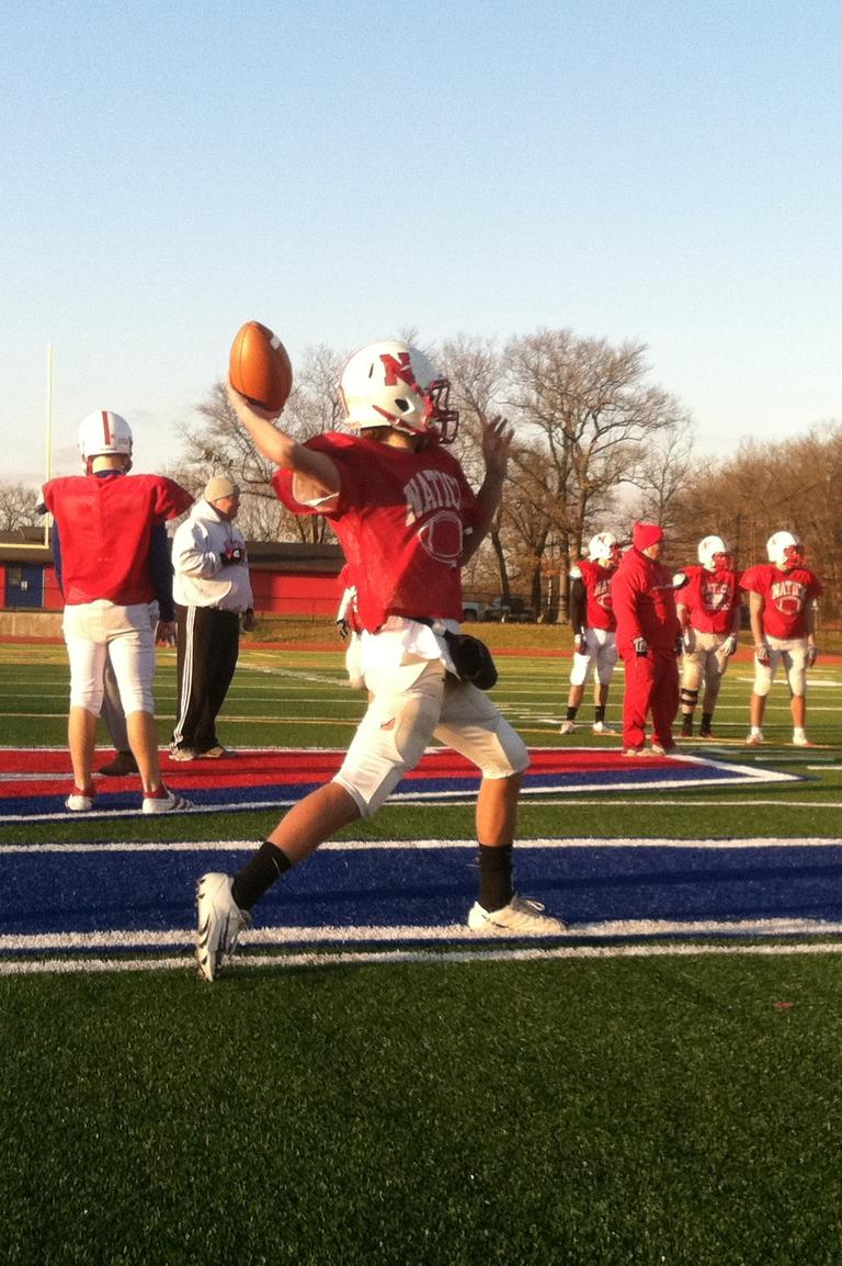 Troy Flutie practices swing passes ahead of Natick's game against Framingham. (Curt Nickisch/WBUR)