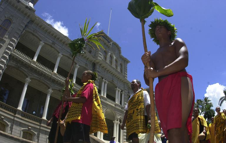 Native Hawaiians march in front of Iolani Palace in Honolulu, Hawaii on September 2, 2002. The march was a celebration of Queen Liliuokalani's birthday.(AP)