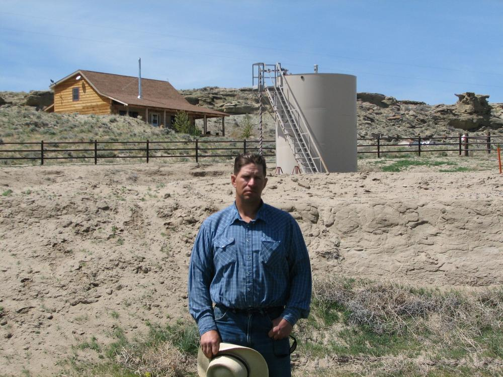 "John Fenton, a farmer who lives near Pavillion in central Wyoming, near a tank used in natural gas extraction, in background. Fenton and some of his neighbors blame hydraulic fracturing, or ""fracking,"" for fouling their well water. (AP)"