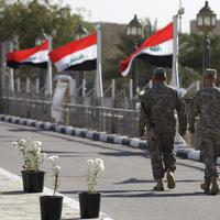 Iraqi flags wave as U.S. soldiers leave Al Faw palace at Camp Victory, one of the last American bases in this country where the U.S.military footprint is swiftly shrinking, after a special ceremony in Baghdad, Iraq, Thursday, Dec. 1. (AP)