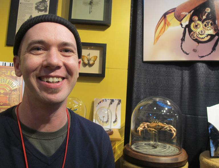 Maine artist Mike Libby, shown at Craftboston, makes intricate insect sculptures using real bugs. (Andrea Shea/WBUR)