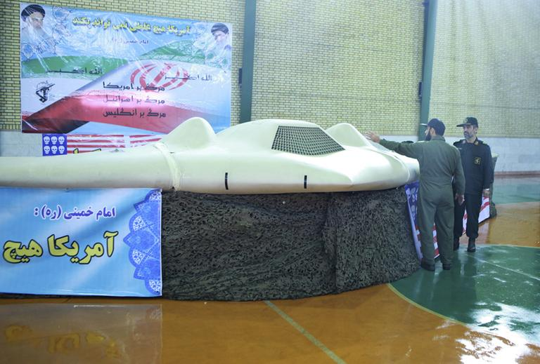 This photo released on Thursday, Dec. 8, 2011, by the Iranian Revolutionary Guards, claims to show US RQ-170 Sentinel drone which Tehran says its forces downed earlier this week, as the chief of the aerospace division of Iran's Revolutionary Guards, Gen. Amir Ali Hajizadeh, right, listens to an unidentified colonel, in an undisclosed location, Iran. (AP)