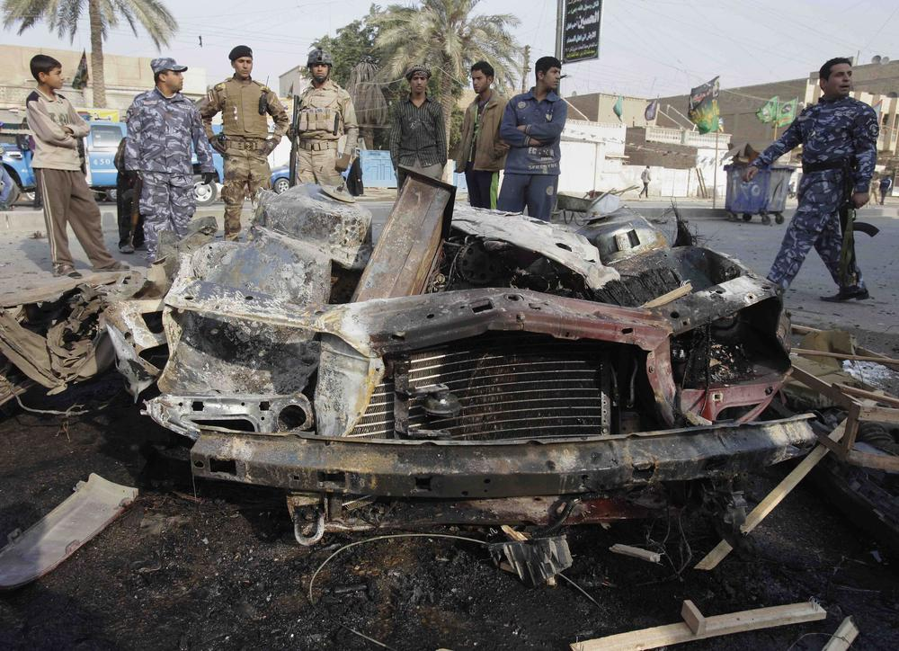 Iraqi security forces and people gather the scene of a car bomb attack in Baghdad, Iraq, Thursday. (AP)