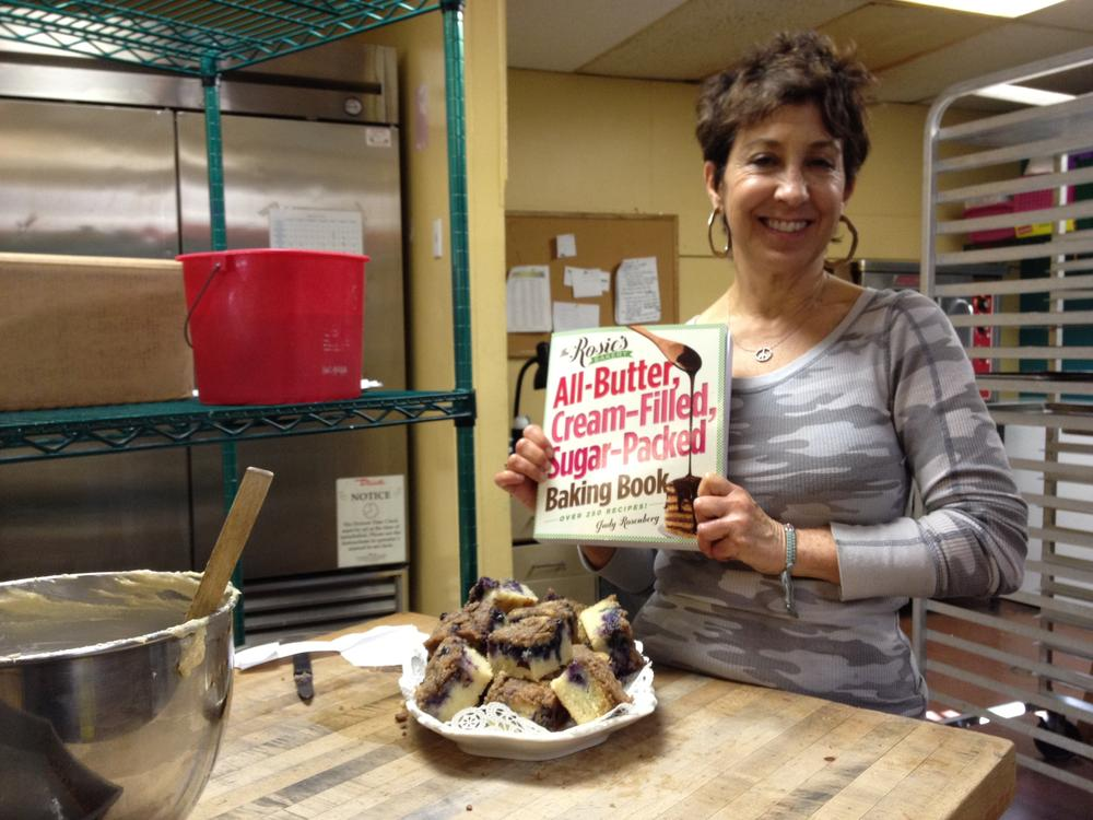 Judy Rosenberg, owner of Rosie's Bakery, at the original Rosie's in Inman Square with her new cookbook and a plate of her fresh Blueberry-Muffin Breakfast Cake. (Adam Ragusea/WBUR)