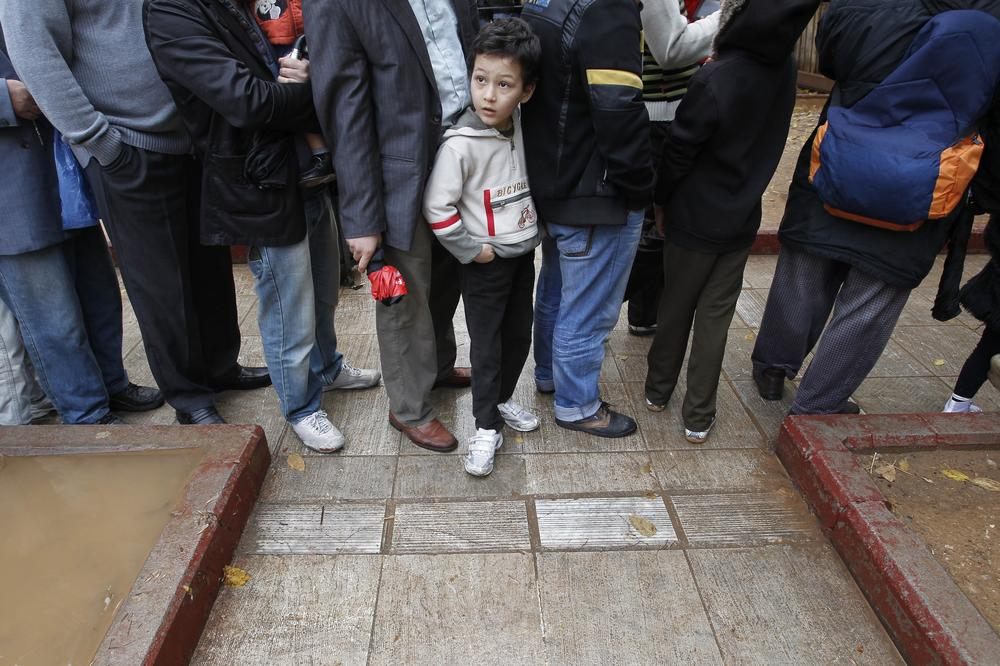 A child waits in line to receive food distributed from the Greek Orthodox Church in Athens, on Thursday. The leader of Greece's Orthodox Church is promising to boost its campaign to provide free meals to the poor and homeless amid the country's deepening financial crisis.(AP)