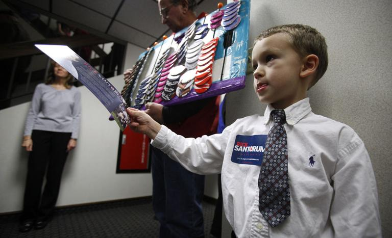 Four-year-old Austin Hall passes out campaign brochures for Republican presidential candidate Rick Santorum in Iowa on Sunday. A new Des Moines Register poll shows Santorum is gaining on front-runners Mitt Romney and Ron Paul. (AP)