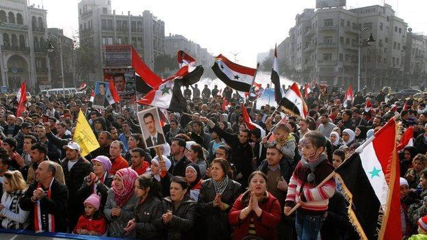 Syria's embattled President Bashar Assad still has supporters, particularly among his fellow Alawites, a minority who believe they will suffer if Assad is ousted. Here, Assad supporters rally Tuesday in the capital, Damascus. (SANA handout / EPA /Landov)