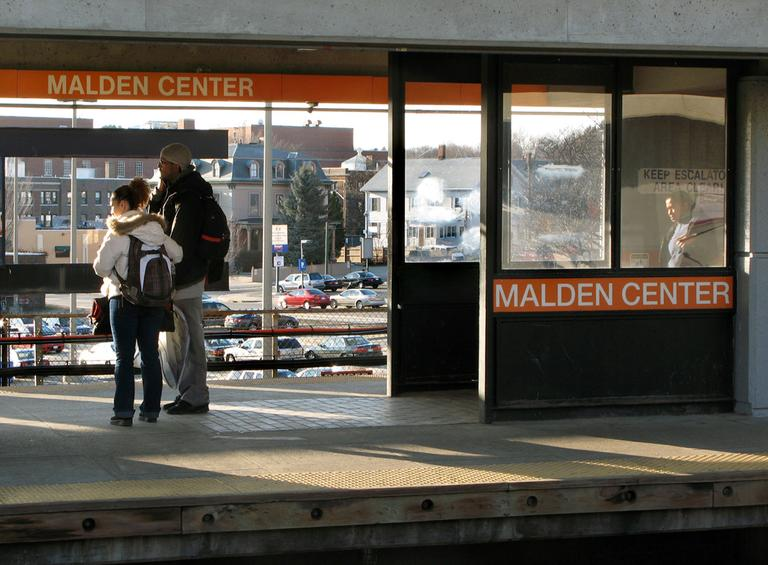 Riders wait on the platform of the MBTA station in Malden in March 2009. (AP)