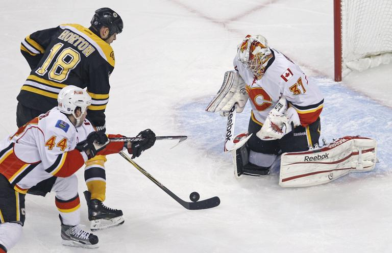 Calgary Flames goalie Leland Irving drops to his pads to make a save on a shot by Boston Bruins right wing Nathan Horton during Thursday night's game. (AP)