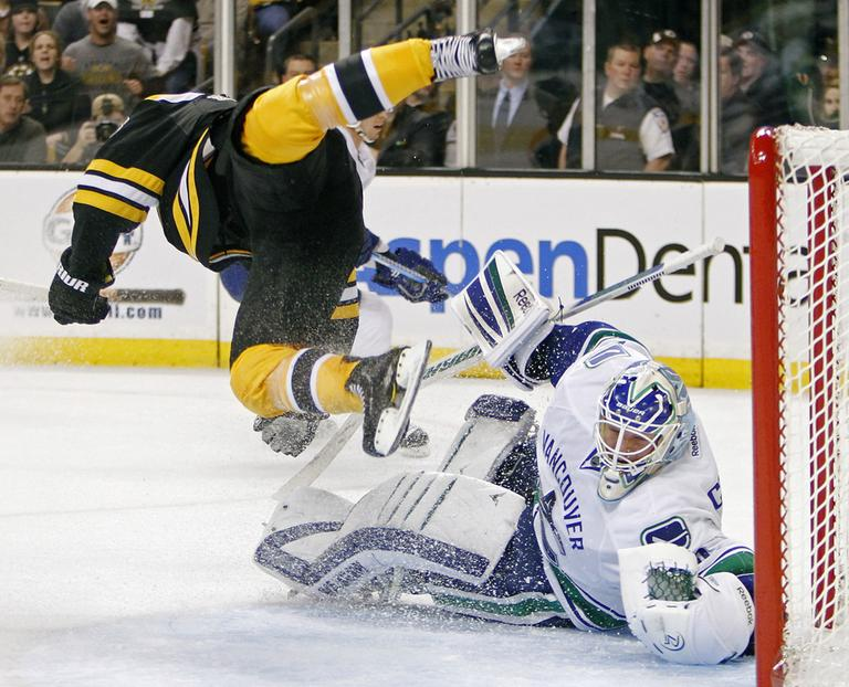 Boston Bruins' Nathan Horton, left, trips over Vancouver Canucks' Cory Schneider in Boston on Saturday. (AP)