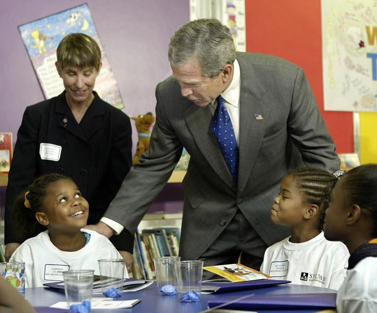 President Bush leans over to speak with third grader Tameron Clark as he tours a tutoring center at Kirkpatrick Elementary School in Nashville, Tenn., in 2003. (AP)
