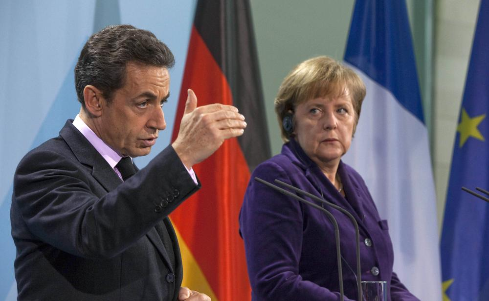 German Chancellor Angela Merkel, right, and French President Nicolas Sarkozy, left, stand next to each other during a news conference at the Chancellery in Berlin, Germany, Monday. (AP)