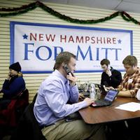 Former Massachusetts Gov. Mitt Romney sits with volunteers and calls likely voters ahead of Tuesday's primary election on Monday. (AP)