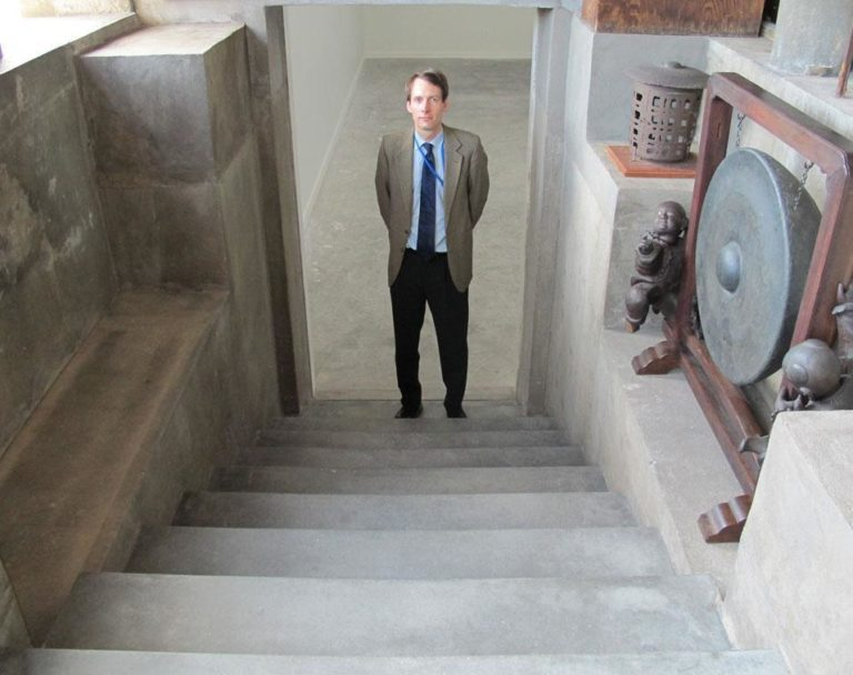 Museum curator Oliver Tostmann, in the steps leading to the hidden room beneath the Chinese loggia (Andrea Shea/WBUR)